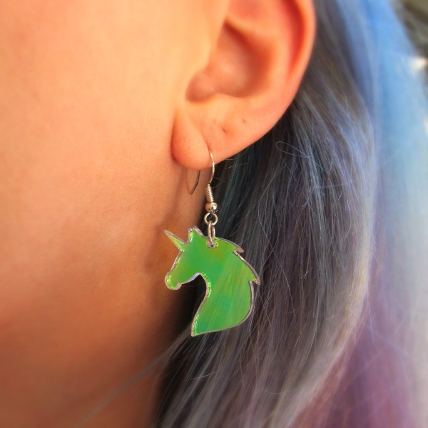 close up of unicorn earring hanging on ear