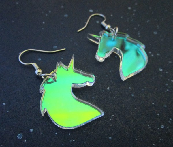 close side view of rainbow unicorn earrings on space background