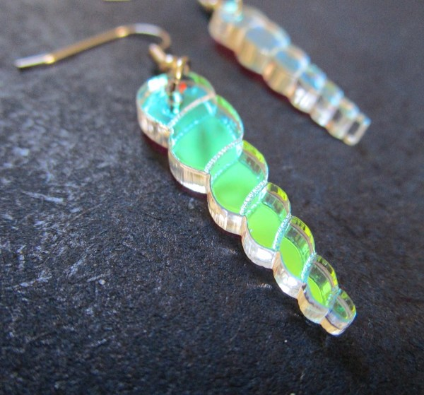 iridescent unicorn horn earrings close up side view on dark background