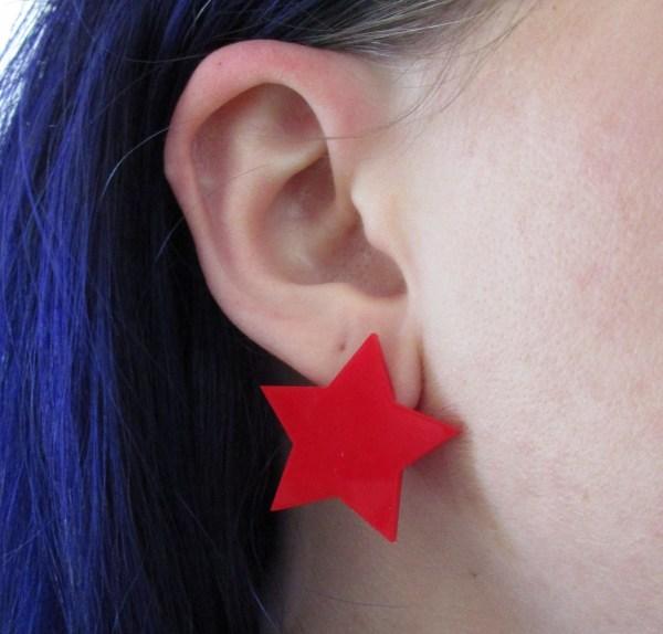 big red star earring in ear