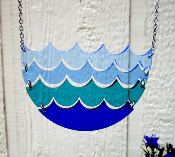 hanging multi layer blue wave necklace with painted wood background