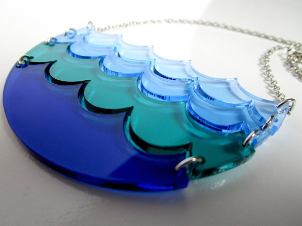 close up of dark blue and teal waves necklace