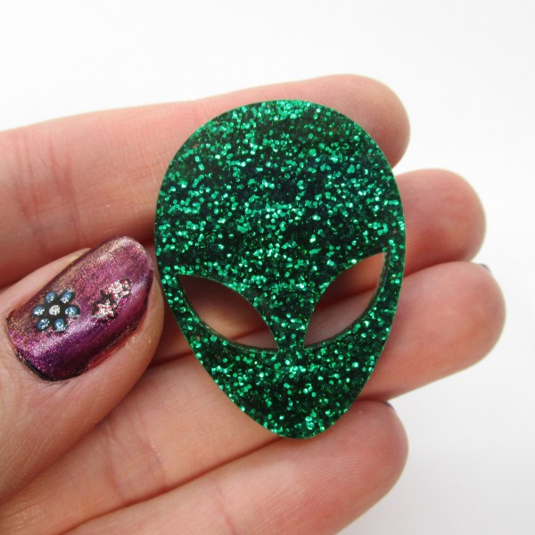 hand holding glitter green alien brooch to show size