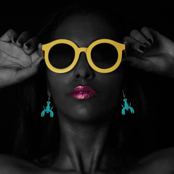 model wearing yellow glasses with pink lips and teal lobster earrings