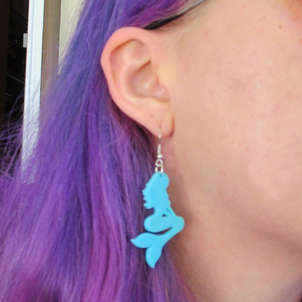 ear wearing teal mermaid dangle earring