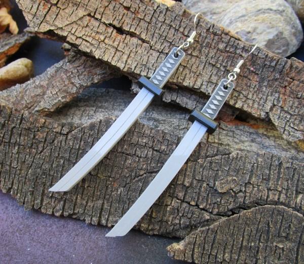 samurai sword katana dangle earrings laying sideways on bark background