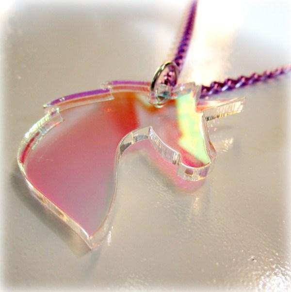 iridescent unicorn pendant laying on white background