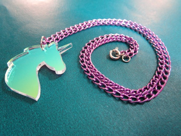 unicorn pendant necklace with purple chain in coil to show lobster claw clasp in teal background