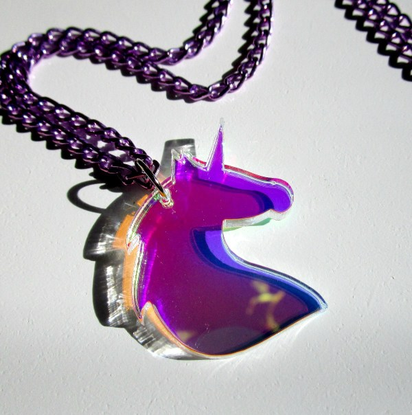 shiny unirorn bust shape pendant on white background with purple chain