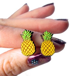 hand holding two yellow pineapple stud earrings to show size