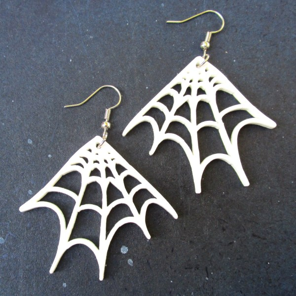 pair of white spider web corner earrings on space background