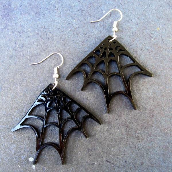 pair of black spider web corner earrings on space background