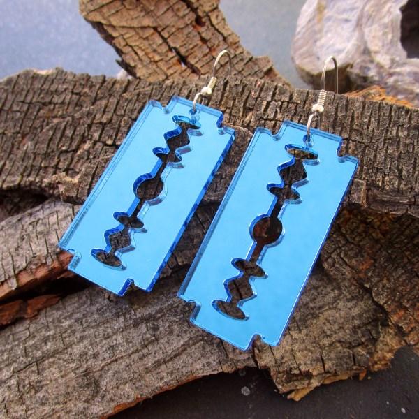 blue double sided razor blade earrings on wood
