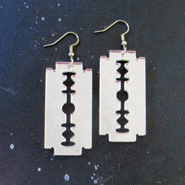 silver razor blade earrings on space background