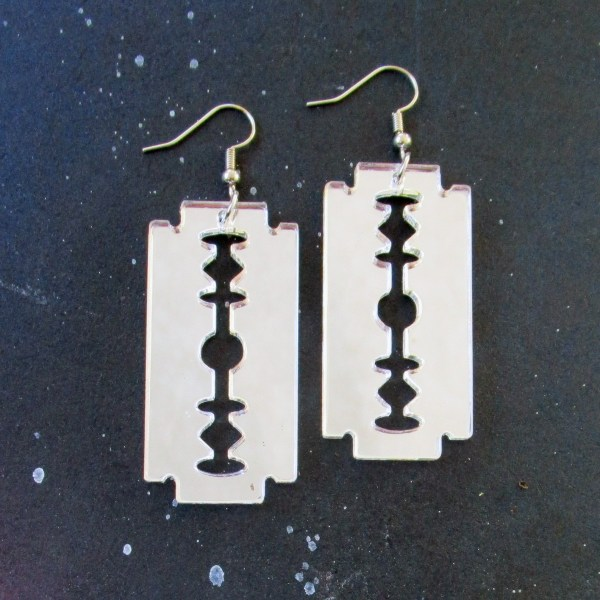 silver razor blade earrings on space background