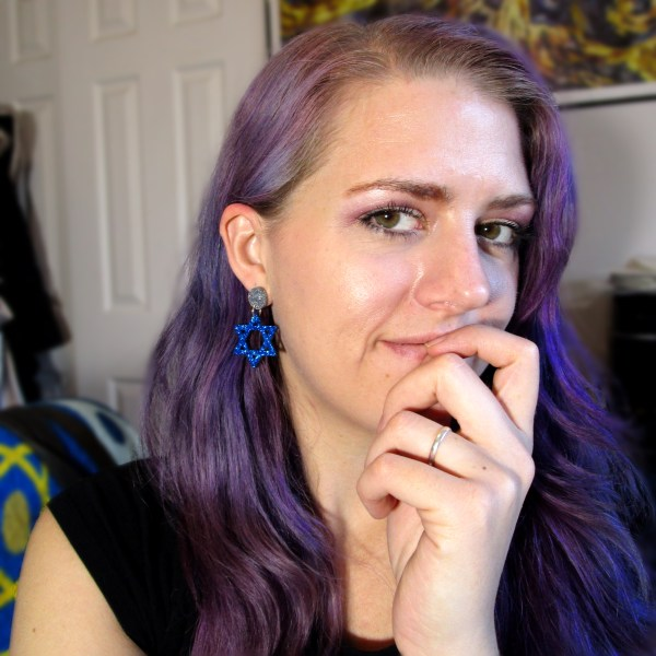 woman being happy about Hanukkah star of davild earrings