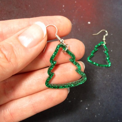hand holding christmas tree outline earrings to show size