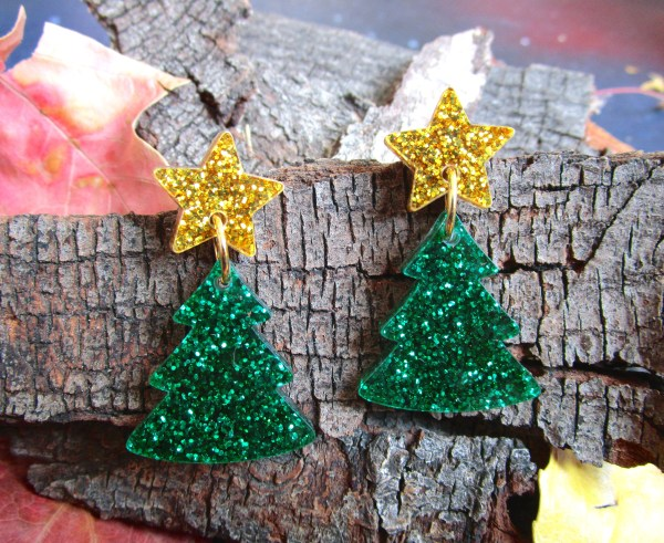 Glitter green christmas tree earrings on wood bark