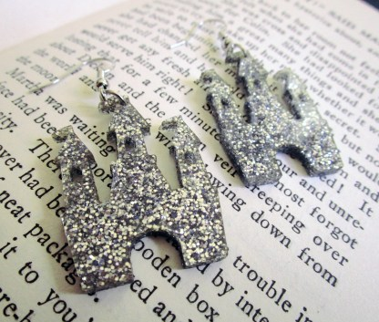 close up of Silver Glitter Magical Princess Castle Earrings on book page