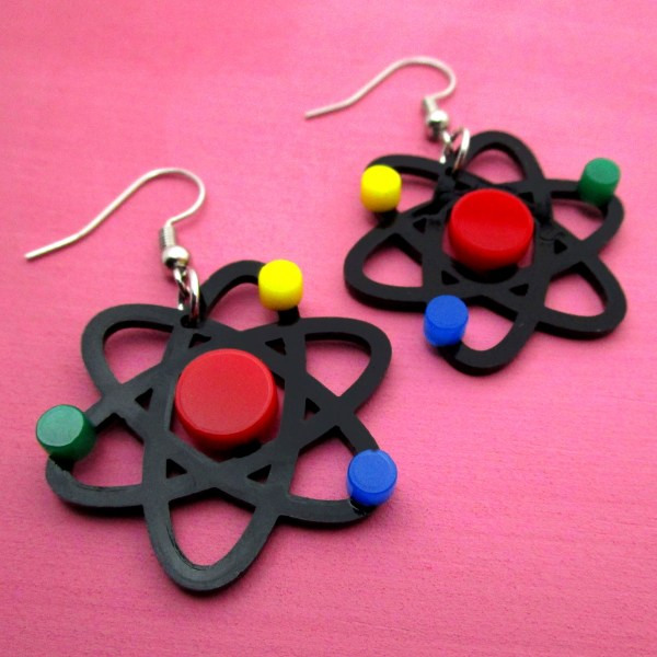 atom earrings on pink background