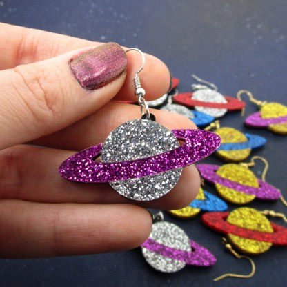 hand holding silver and purple glitter planet earring with other color combinations in background