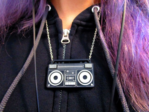 close up of boom box pendant necklace being worn over black hoodie