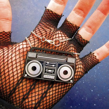 hand with fishnet glove holding retro boombox pendant necklace