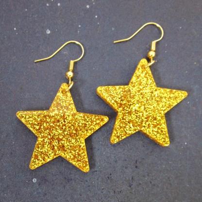 big gold glitter dangle star earrings
