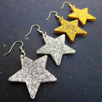 diagonal row of glitter star earrings in gold and glitter