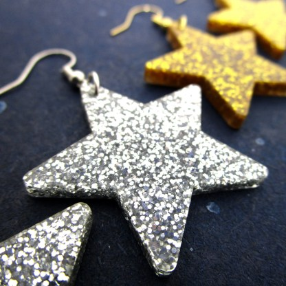 up close silver glitter star earrings with gold earrings in distance