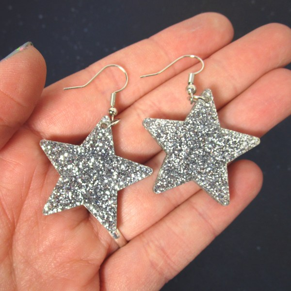 hand holding pair of silver glitter star earrings