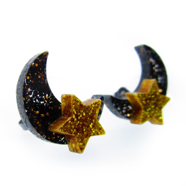 sideways view of black moon and gold star earrings