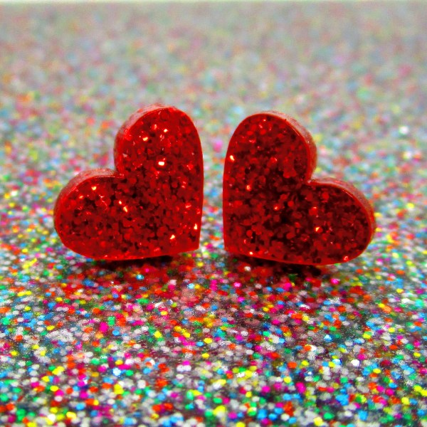 little red glitter heart stud earrings on glitter background