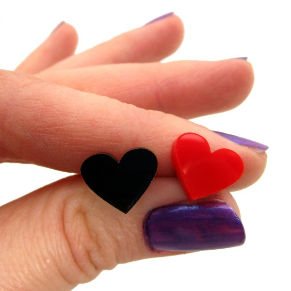 hand holding red and black heart stud earring to show size