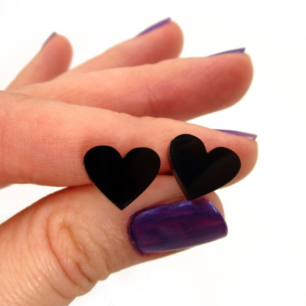 hand holdin pair of small black heart earrings to show size