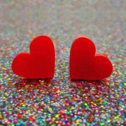 red heart earrings on glitter surface