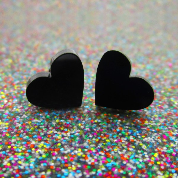black heart earrings on glitter surface