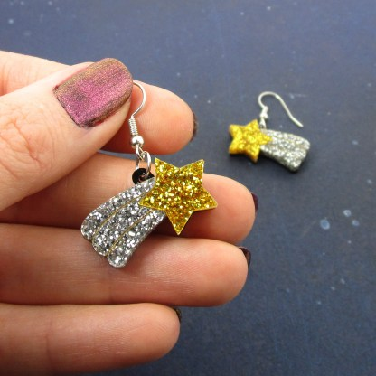 hand holding statement earrings of shooting stars with glitter