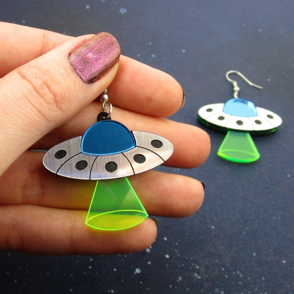 hand holding ufo with abduction beam earrings