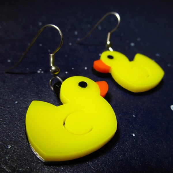 yellow rubber ducky earrings on space background