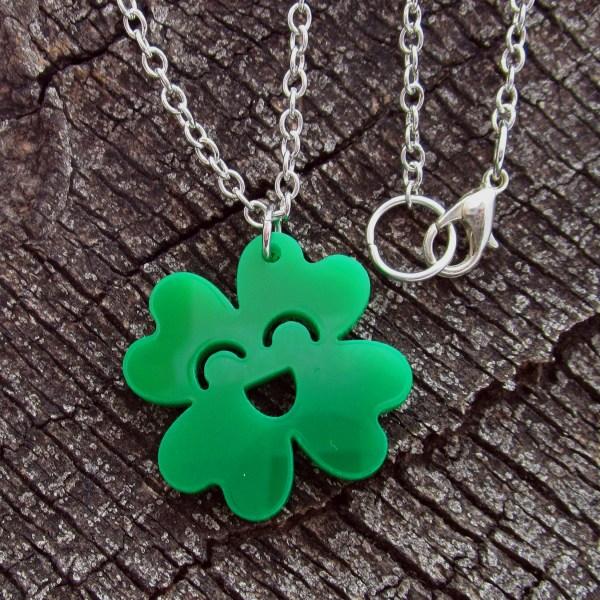 happy 4 leaf clover pendant necklace on wood background