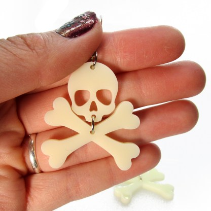 hand holding skull with crossbones earring to show size