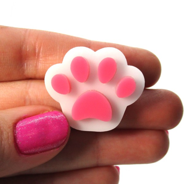 hand holding white paw with pink pads brooch