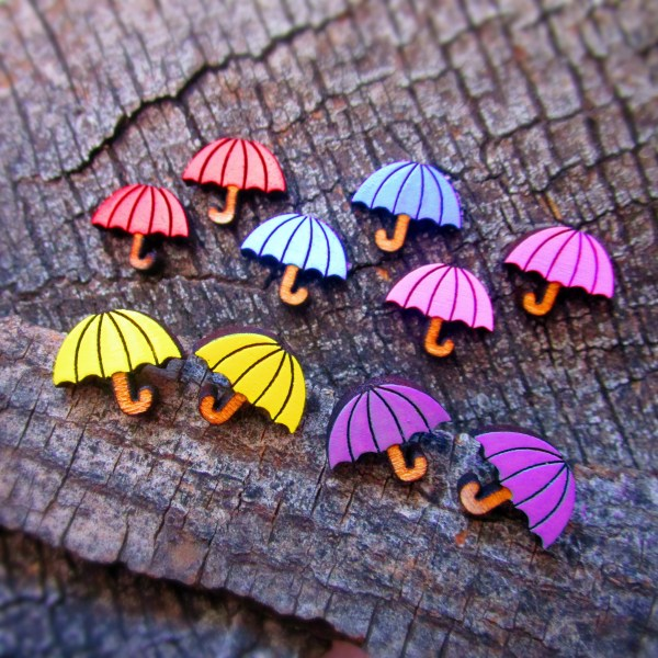 bunch of colorful umbrella earrings on wood background