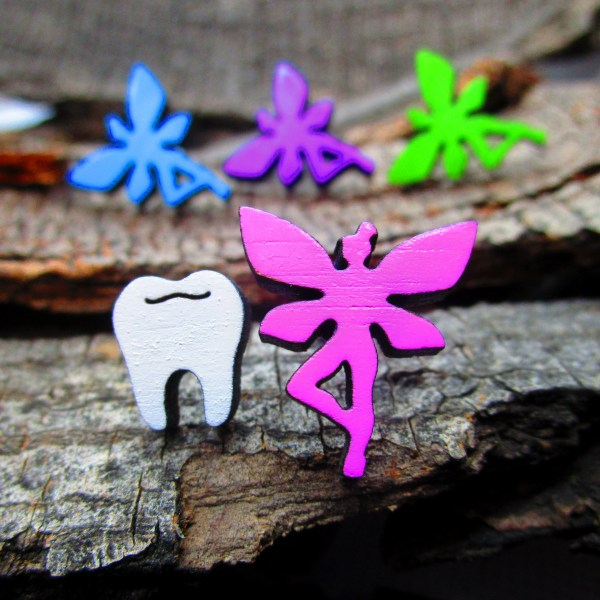 close up of pink fairy and tooth earrings set