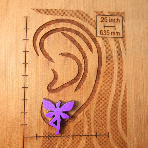 purple fairy earring on ear board to show size