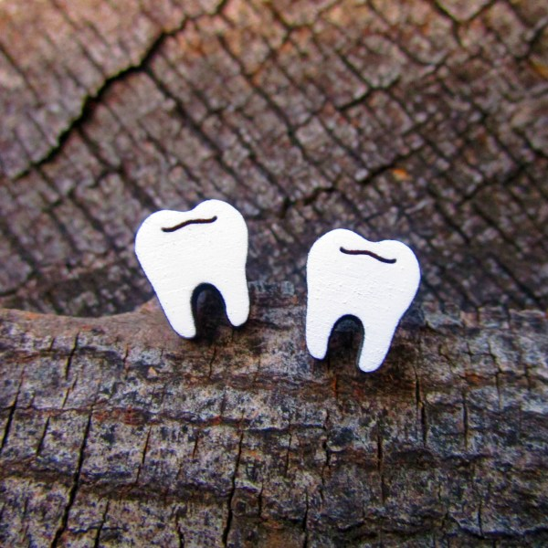 pair of white tooth earrings on wood background