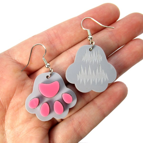 hand holding gray paw print cat paw earrings to show size