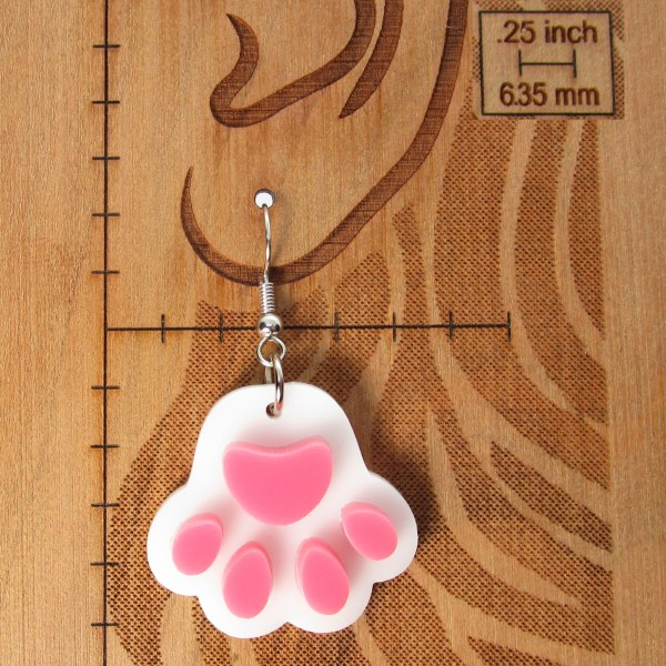 white cat paw print earring on board with measurements