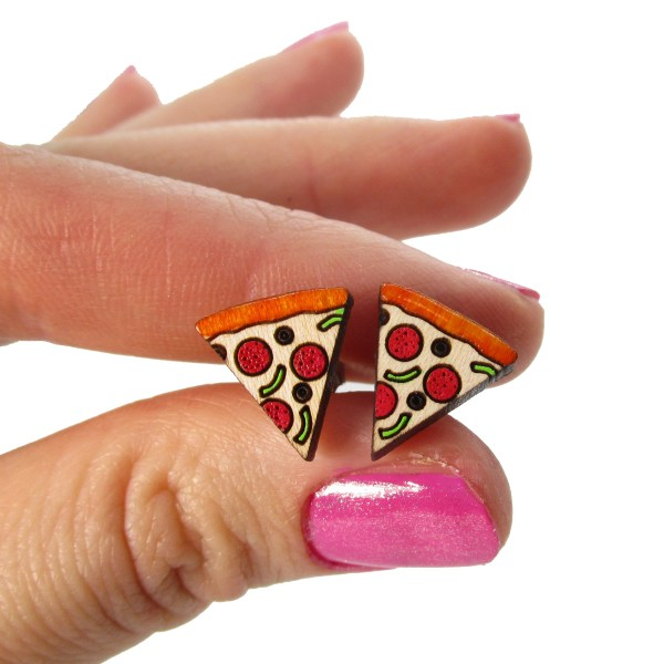 hand holding pizza stud earrings to show size